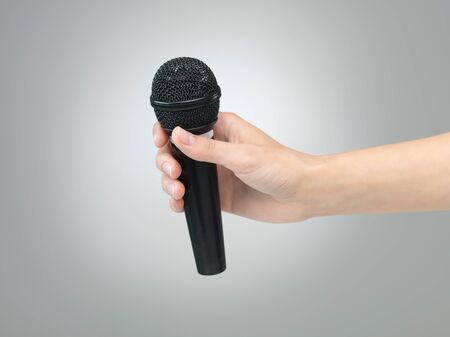Hand with microphone on neutral grey gradient background photo