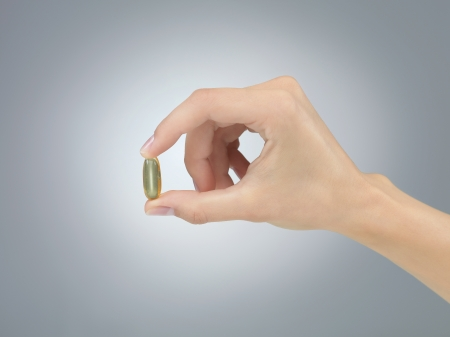 pill in fingers neutral gray gradient background photo
