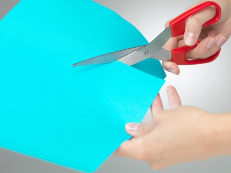 hands cutting a shape from a blue paper with a pair  of red scissors on neutral grey background photo