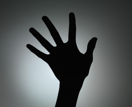 five fingers: hand silhouette with fingers spread backlit on grey gradient background Stock Photo