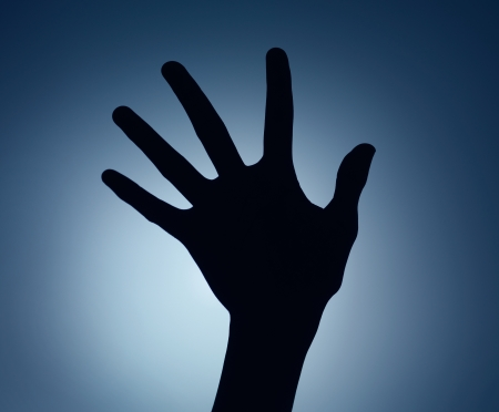 hand lifted: hand silhouette with fingers spread backlit on blue gradient background