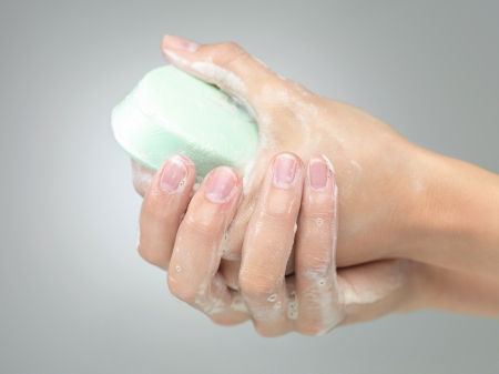 female women washing her hands with soap on grei gradient background photo