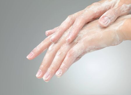 closeup of female hands with soap foam on grey gadient background photo