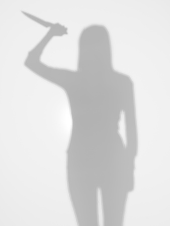 female silhouette holding a knife in her hand with a gesture of attack, behind a diffuse surface photo