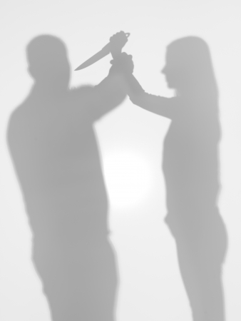 domestic scene: body silhouettes, woman trying to stab a man with a kitchen knife, domestic violence scene, behind a diffuse surface Stock Photo
