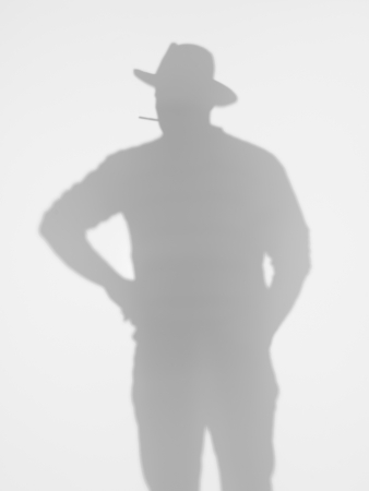 man silhouette standing and posing with a cowboy hat and smoking a cigarette behind a diffuse surface photo