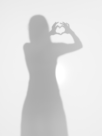female body silhouette creatind a heart shape with her hands, behind a diffuse surface Stock Photo - 17884456