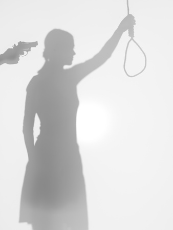 threatened: female body silhouette holding a strangling rope while beeing threatened with a gun, behind a diffuse surface