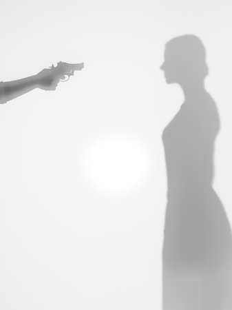 death head holding: woman body silhouette standing, beeing thretened with a gun, behind a diffuse surface Stock Photo
