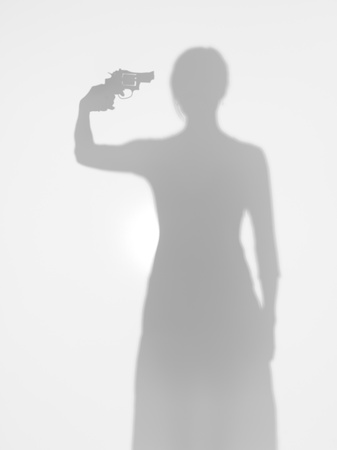 young female body silhouette standing and aiming a gun towards her head, behind a diffuse surface photo