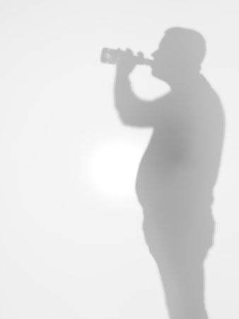 side view of adult man drinking beer from a glass bottle behind a diffuse surface photo
