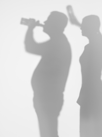 side view of grownup man drinking beer from a glass bottle with a woman behind him trying to hit him in the head with a beer bottle, silhouettes photo