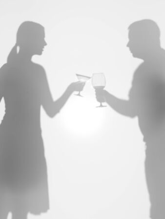 two people silhouettes holding two different glasses, behind a diffuse surface, cheers Stock Photo - 17884570