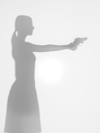 merciless: side view of woman silhouette holding a handgun aiming in front of her, behind a diffuse surface