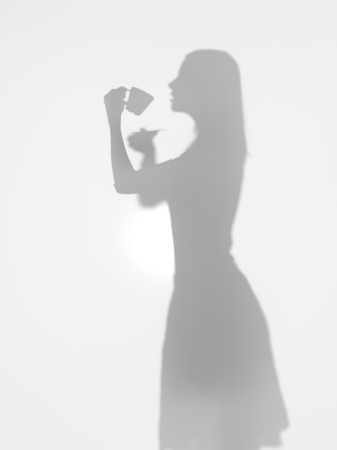side view of woman silhouette drinking a cup of coffee behind a diffuse surface photo
