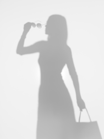 girl shadow: side view of elegant slim woman holding a bag and a pair of sunglasses in her hand, behind a diffuse surface, silhouette
