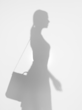side view of young business woman with shoulder bag, walking behind a diffuse surface photo