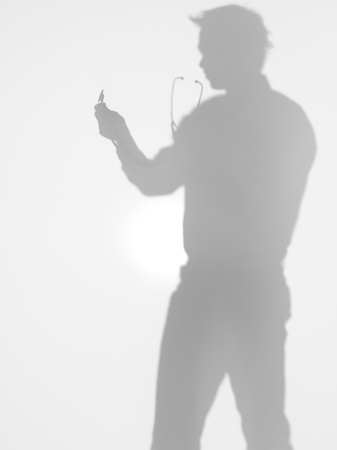 side view of man holding a stethoscope in his hands in front of him, behind a diffuse surface photo