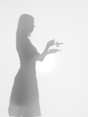 genie lamp: side view of woman holding the lamp of alladin in her hands, behind a diffuse surface Stock Photo
