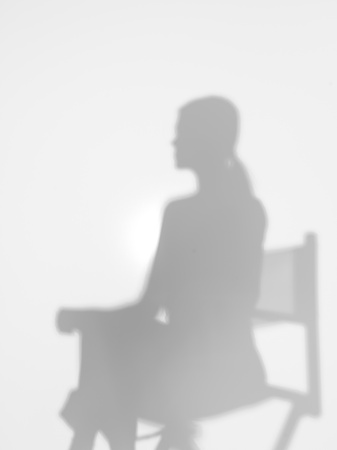 woman sitting on a directors chair, behind a diffuse surface, back lit photo