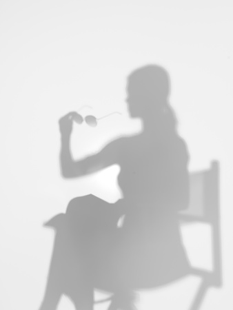 director chair: woman sitting on directors chair reading a book with sunglasses in her hand, behind a diffuse surface Stock Photo