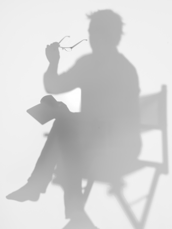 director chair: man sitting on directors chair reading a book with eyeglasses in his hand, behind a diffuse surface