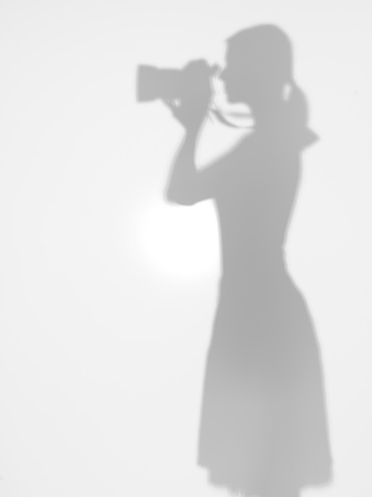 side view of woman holding a photographic camera in her hands looking throw the viewfinder, behind a diffuse surface photo