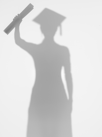 female graduating student standing and proudly showing her diploma, behind a diffuse surface photo