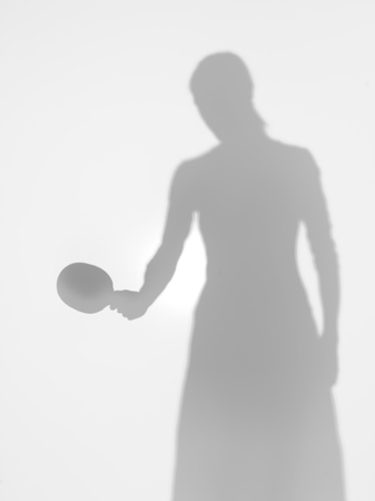 woman silhouette standing holding a table tennis racquet in one hand, behind a diffuse surface photo