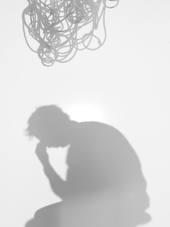 diffuse: side view of man sitting with a thinking gesture, with tangled rope on top of him, behind a diffuse surface