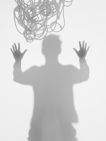 stuck up: front view of man holding his hands up, wanting to break free, with tangled rope on top of his head, behid a diffuse surface
