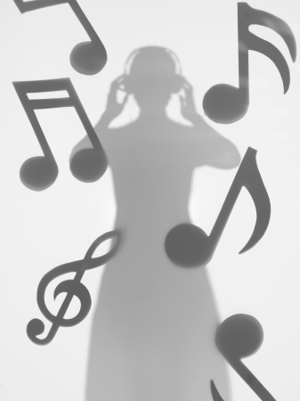 woman standing and listening music with headphones, between musical notes, behind a diffuse surface photo