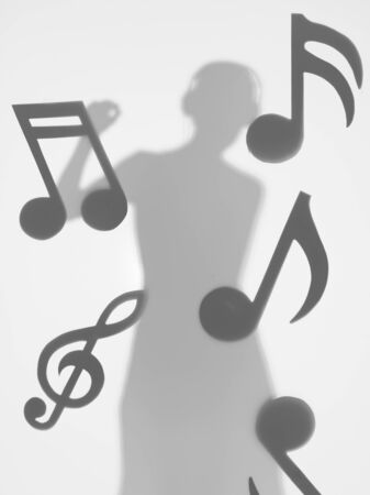 woman dancing and listening to music with headphones, surrounded by musical notes, behind a diffuse surface photo
