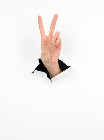 coming out: close-up of female hand coming out from a hole in a paper, peace sign, isolated Stock Photo