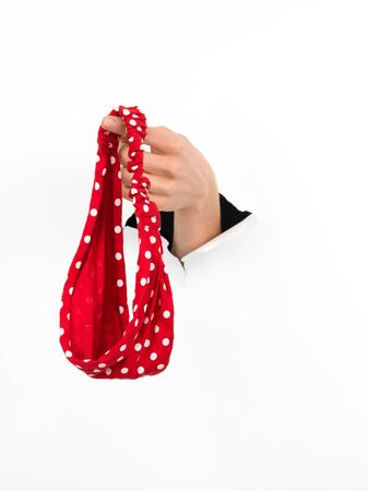 close-up of female hand coming out from a hole in a paper, holding a red dotted headband, isolated on white photo