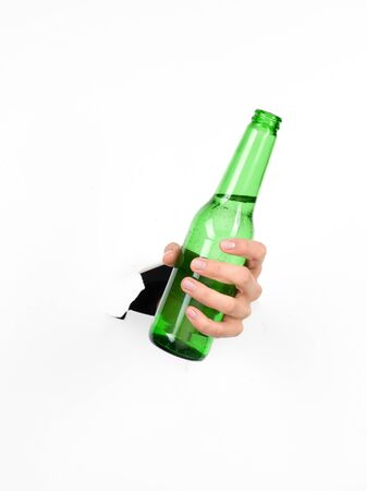 broken through: close-up of female holding a green beer bottle through a white paper, isolated