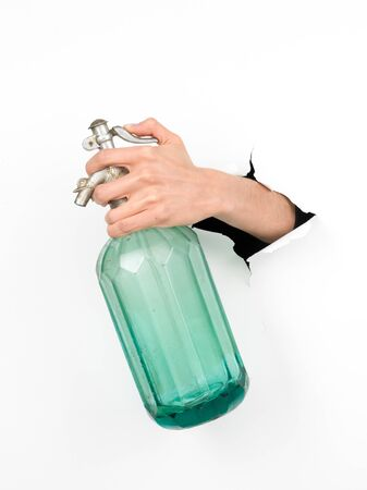 close-up of female hand holding a vintage soda bottle through a white paper, isolated photo