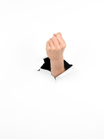 female fist through a hole in a white paper, tough gesture, isolated photo