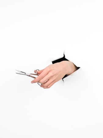close-up of female hand holding a pair of scissors through a white paper, isolated photo