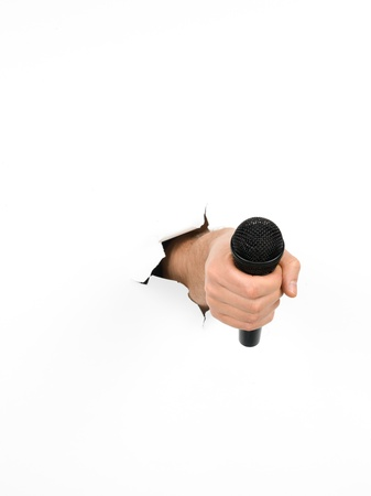 close-up of male hand holding a black microphone through a torn white paper, isolated Stock Photo - 18566027