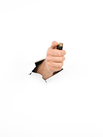 close-up of male hand holding a black lighter through a torn white paper, isolated Stock Photo - 18555608
