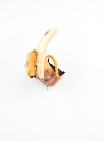 close-up of male hand holding a peeled banana through a torn white paper, isolated photo