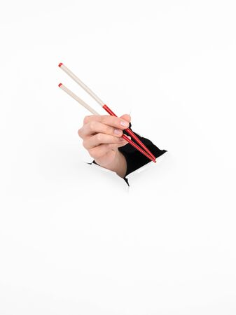 close-up of female hand holding chopsticks through a torn white paper photo
