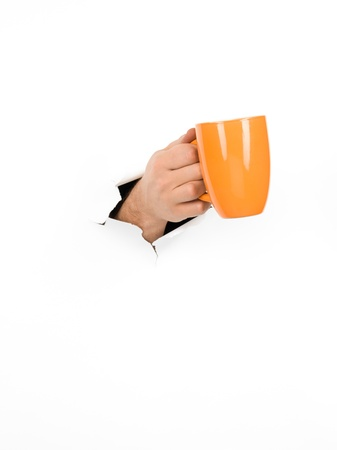 close-up of male hand holding a cup through a torn white paper, isolated photo