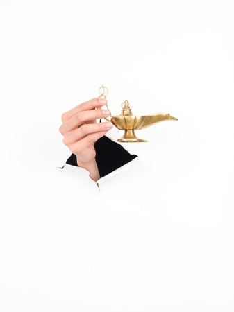 alladdin: close-up of female hand holding a magic lamp through a torn white paper, isolated Stock Photo
