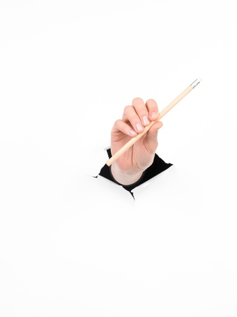 close-up of female hand holding a pencil through a torn white paper, isolated photo