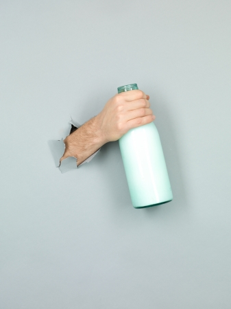 close-up of male hand holding a green bottle with milk through a grey torn paper photo