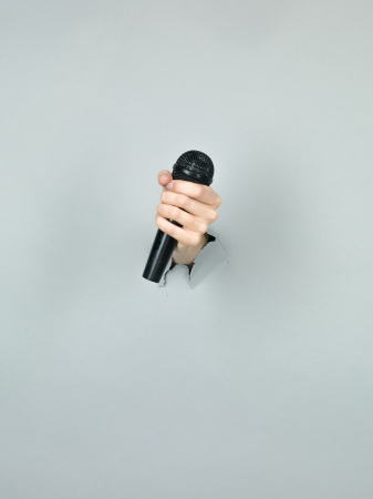 close-up of girl hand holding a black microphone through a torn grey paper photo