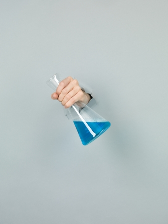 femal: close-up of femal hand holding a chemistry flask with blue liquid in it through a torn grey paper