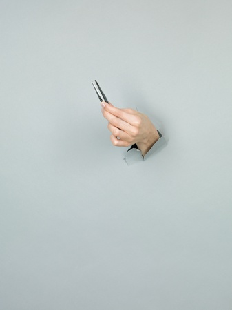 close-up of female hand holding a tweezers through a torn grey paper photo